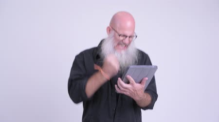 raising fist : Happy mature bald bearded man using digital tablet and getting good news
