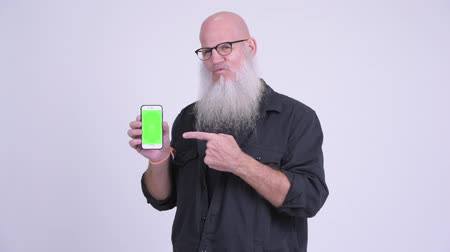 vlogging : Happy mature bald bearded man showing phone and giving thumbs up Stock Footage