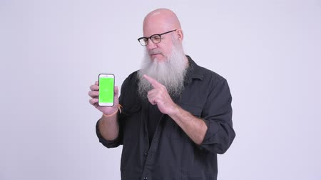 calvizie : Sad mature bald bearded man showing phone and giving thumbs down