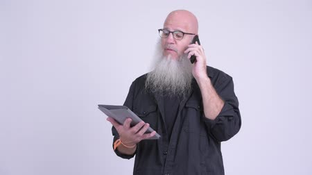 vlogging : Mature bald bearded man using digital tablet and phone Stock Footage