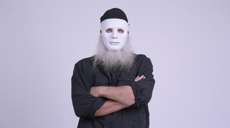 to disguise : Mature bearded hipster man wearing white mask as Halloween concept