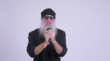 певец : Mature bearded hipster man singing with microphone as rock star concept