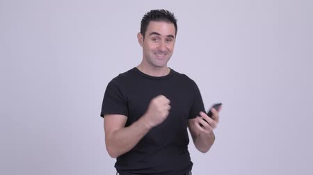 kabarık : Happy handsome man using phone and getting good news Stok Video