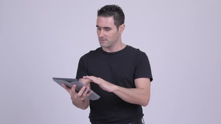 raising fist : Happy handsome man using digital tablet and getting good news Stock Footage