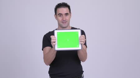 átnyújtás : Happy handsome man showing digital tablet against white background