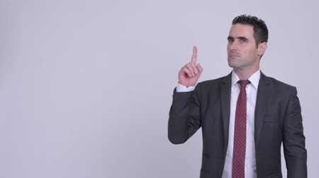 olhando para cima : Handsome businessman thinking while pointing up Stock Footage