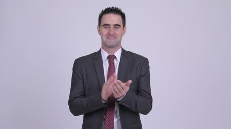 ovation : Happy handsome businessman clapping hands against white background