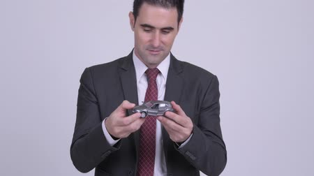 в середине : Handsome businessman holding toy car against white background Стоковые видеозаписи