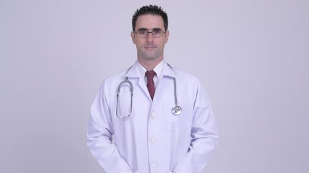 physician : Happy handsome man doctor smiling against white background