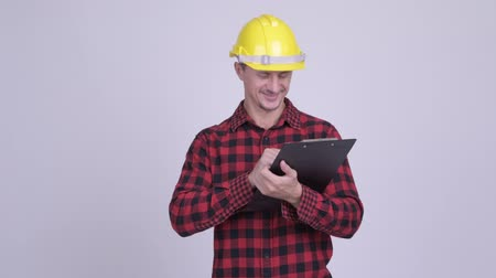 přímý : Happy bearded man construction worker reading on clipboard and directing Dostupné videozáznamy