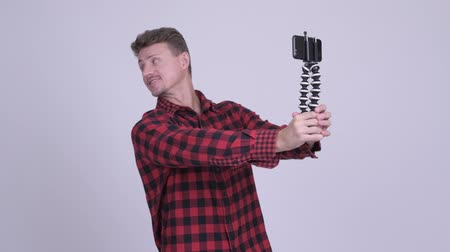 tripod shot : Happy handsome bearded hipster man vlogging with phone