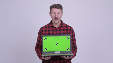 vay : Happy bearded hipster man looking surprised while showing laptop Stok Video