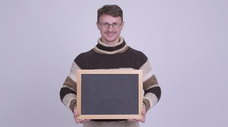 anız : Happy handsome bearded man holding blackboard ready for winter Stok Video