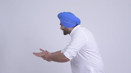 turban : Happy young bearded Indian Sikh man showing something