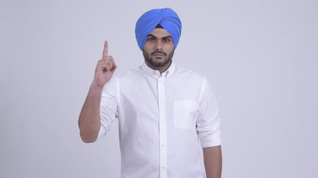 sikhism : Young bearded Indian Sikh man pointing up