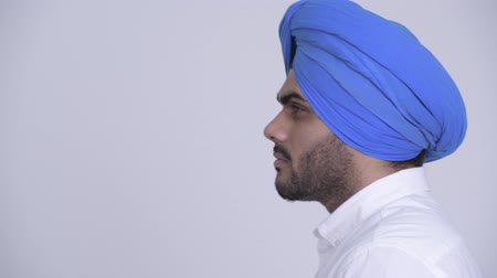 головной убор : Closeup profile view of happy young bearded Indian Sikh man thinking Стоковые видеозаписи