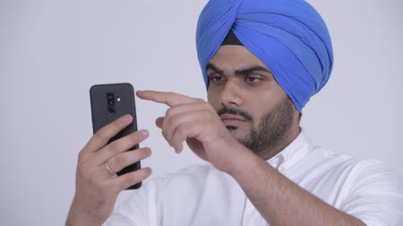 frizura : Face of young bearded Indian Sikh man using phone