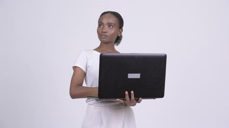 south african : Happy young beautiful African woman thinking while using laptop Stock Footage