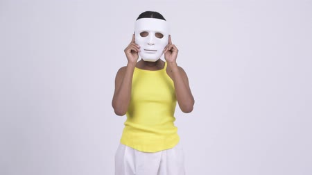 to disguise : Happy young African woman removing white mask