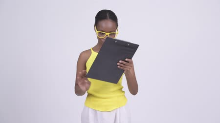 siyah üzerine izole : Young angry African woman reading and showing clipboard Stok Video
