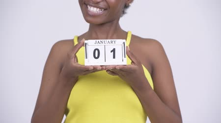 etnia africano : Young happy African woman holding calendar block ready for New Years