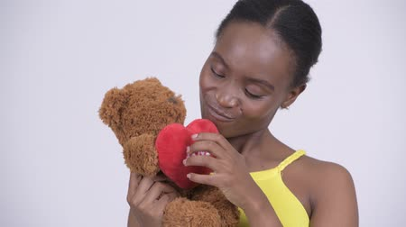 infantil : Young happy African woman holding teddy bear and acting childlike