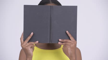 gizleme : Young beautiful African woman hiding behind book Stok Video