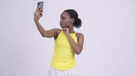 etnia africano : Happy young beautiful African woman taking selfie with phone Stock Footage
