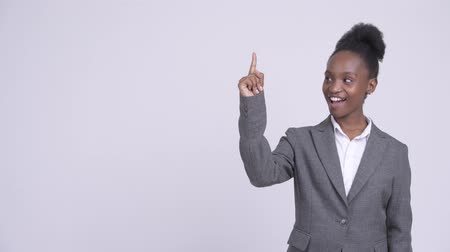 задумчивый : Young happy African businesswoman thinking and pointing up