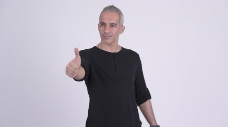 sörte : Handsome Persian man giving thumbs up against white background
