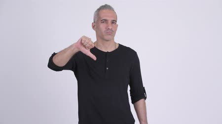 anız : Serious Persian man giving thumbs down against white background