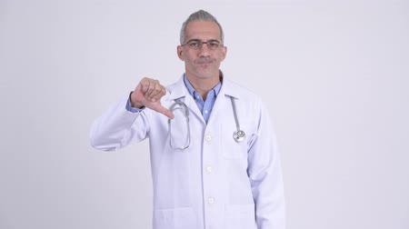 refusing : Stressed Persian man doctor giving thumbs down against white background Stock Footage