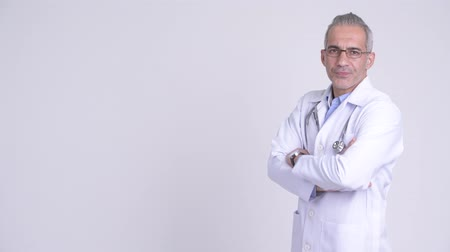 hanedan arması : Profile view of happy Persian man doctor looking at camera Stok Video
