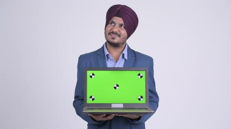 turban : Happy bearded Indian Sikh businessman thinking while showing laptop