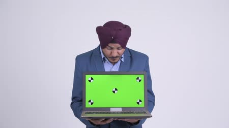 sikhism : Happy Indian Sikh businessman showing laptop and looking surprised