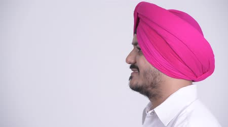 sikhism : Profile view of happy bearded Indian Sikh man smiling while wearing turban