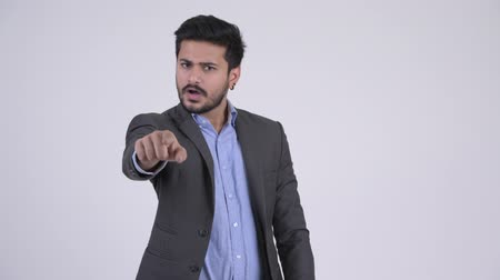 öfkeli : Young angry bearded Indian businessman talking and pointing at camera