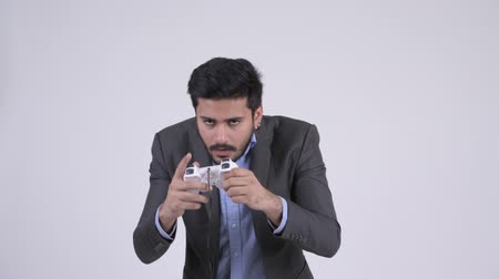 perdedor : Young stressed bearded Indian businessman playing games and losing