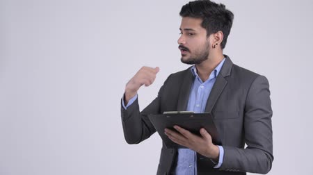 přímý : Young bearded Indian businessman directing while holding clipboard Dostupné videozáznamy
