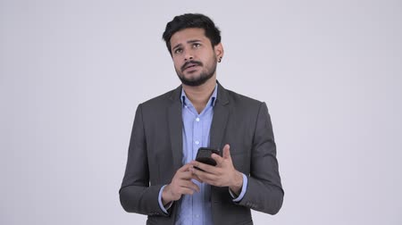 vlogging : Young happy bearded Indian businessman thinking while using phone