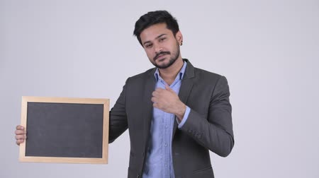удовлетворения : Young happy bearded Indian businessman showing blackboard and giving thumbs up