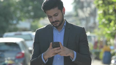 on the phone : Young happy bearded Indian businessman using phone outdoors Stock Footage