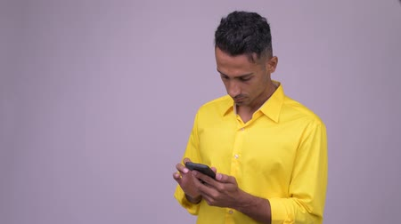 vlogging : Young handsome Persian businessman with yellow shirt using phone Stock Footage