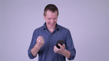 fince : Happy young handsome businessman using phone and getting good news