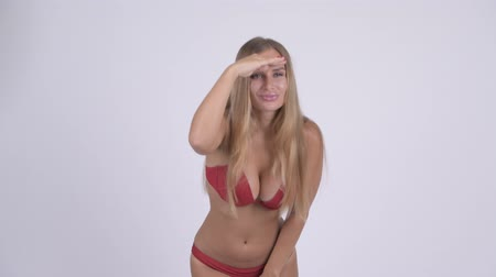 daleko : Young beautiful blonde woman in bikini searching for something