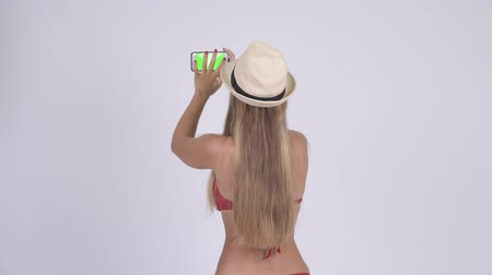 tomar : Rear view of young blonde tourist woman in bikini taking picture with phone
