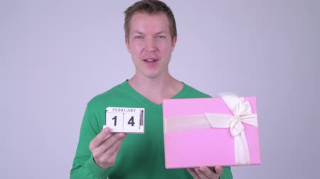 フィンランド語 : Happy young handsome man with calendar block and gift box 動画素材