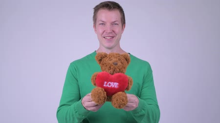 плюшевый мишка : Happy young handsome man with teddy bear ready for Valentines day Стоковые видеозаписи