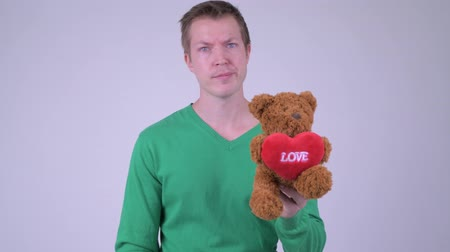 refusing : Portrait of young stressed man giving thumbs down with teddy bear