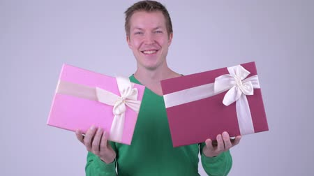 fince : Happy young handsome man with two gift boxes ready for Valentines day Stok Video